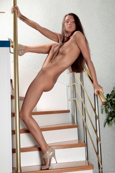 Голая девушка позирует на лестнице