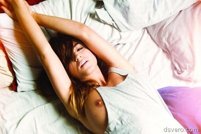 Девушка с голой грудью в кровати