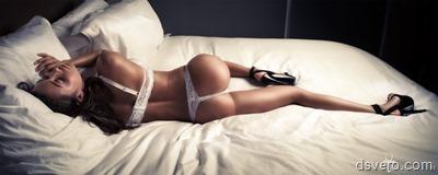 Стройная девушка позирует в кровати