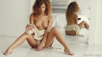 Голая молодая девушка с айфоном