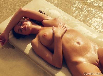 Голая мокрая девушка на лежаке в воде