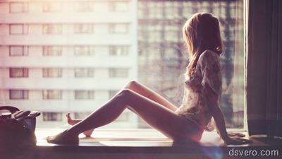 Стройная девушка сидит и смотрит в окно