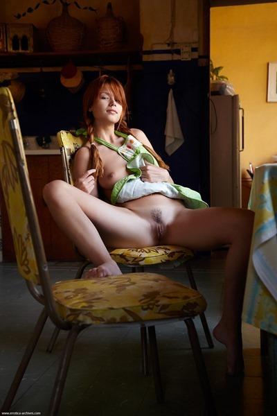 Голая рыжая девушка в фартуке на кухне