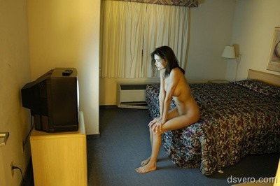 Молодая голая девушка в комнате отеля